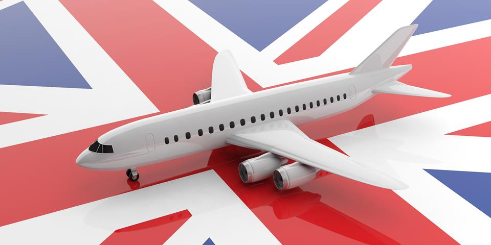 Miniaturowy biały samolot stojący na fladze Wielkiej Brytanii