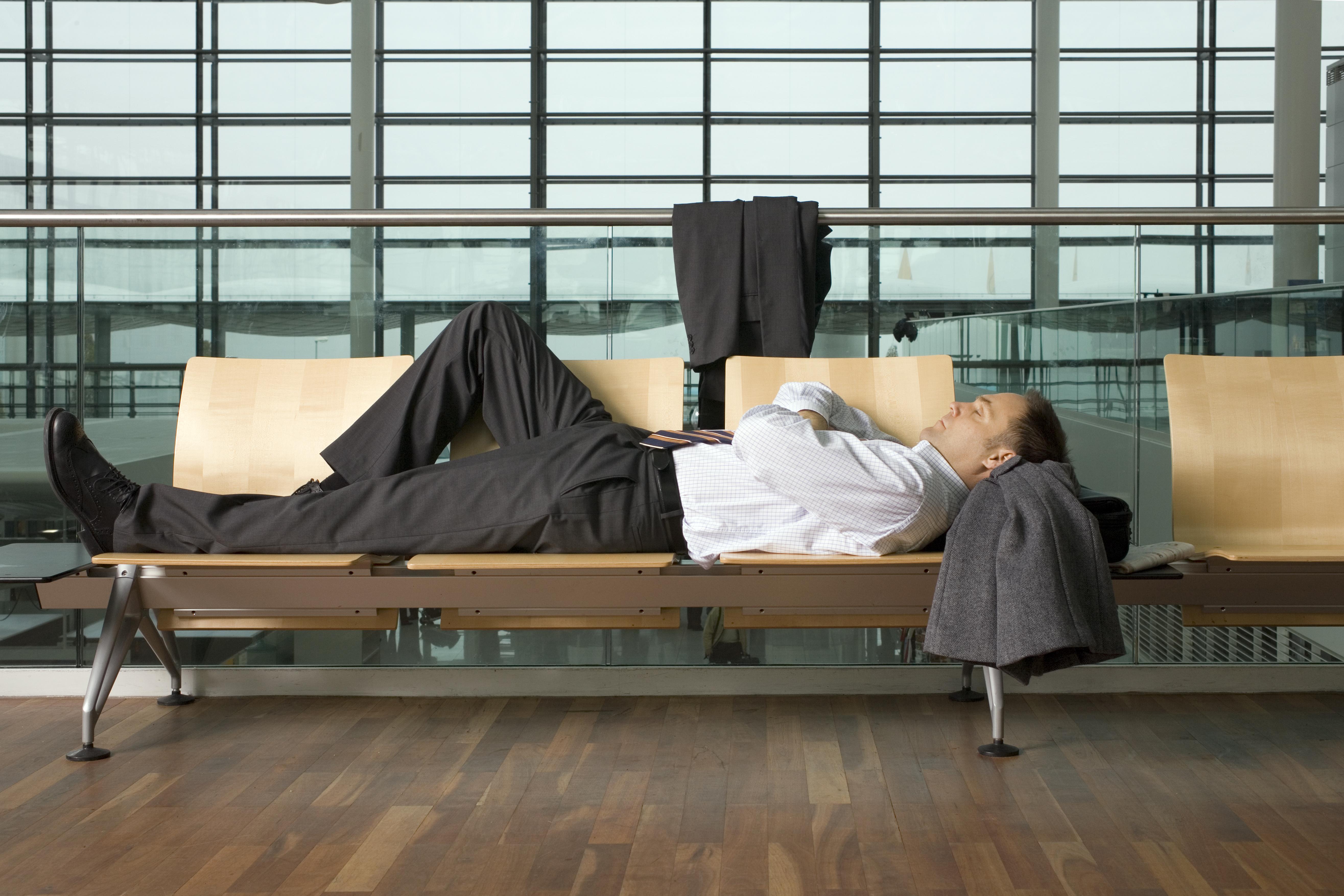Mężczyzna w garniturze śpiący na lotnisku.