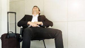 Młody mężczyzna z walizką śpiący na lotnisku.