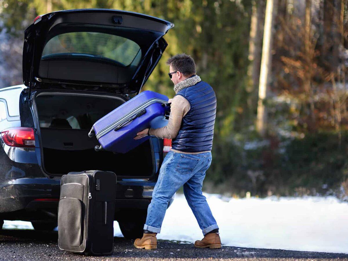 Mężczyzna pakuje bagaże do samochodu przed wyjazdem na urlop