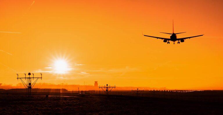 Sylwetka samolotu lądującego o zachodzie słońca na lotnisku Kraków Balice